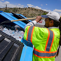 City of Gallup solid waste department Duriel Boyd rakes through a bin full of plastic bottles while tending the recycling station on Montoya Boulevard in Gallup Saturday.