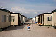 Castel Romano, Gypsy Container Camp on the edge of Rome. Many were evicted from Vicolo Savini within Rome and moved here. Roma Gypsies victims of racism and discrimination, often forcibly evicted or moved from one camp to another, marginalized, living on the periphery of urban centres. The Roma Gypsies originated from India where they left over a thousand years before. Tribes moved across Euroasia eventually arriving in Europe in the 14th century. They have survived 500 years of slavery and persecution. They moved from place to place, often nomadic in search of work. Now many live in container camps, some are unemployed, others work the markets, or import export. Rome, Italy.