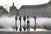 Place de la Bourse. The new fountain Miroir d'Eau, Water Mirror, making reflections. People playing in the mist fog. Bordeaux city, Aquitaine, Gironde, France