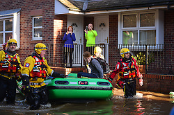 © Licensed to London News Pictures. 27/12/2015. York, UK.  A resident is evacuated by a mountain rescue team from a flooded street in York City centre. Large areas of the North of England have been hit by severe flooding following unusually heavy rainfall in December. Photo credit: Ben Cawthra/LNP