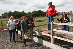 Woman with visual impairment having riding lesson, about to get on horse.