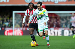 Brentford's Romaine Sawyers (left) and Norwich City's Mario Vrancic battle for the ball during the Sky Bet Championship match at Griffin Park, London.