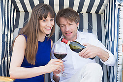 Couple having vine in roofed wicker beach chair, smiling