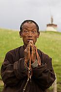 A man prays with Tibetan Buddhist prayer beads near Litang, Tibet.