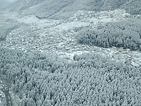 Aerial view of snow-capped old Manali neighbourhood sourrounded by pine trees forest in Himachal pradesh of India.