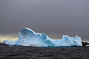 Carved blue iceberg with grey cloud