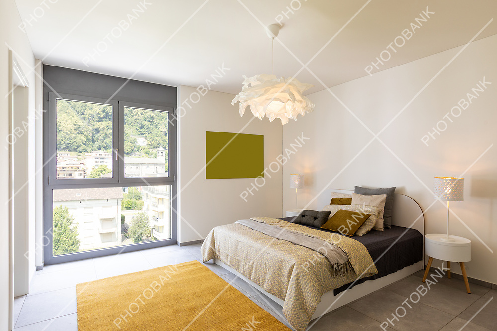 Interior of elegant double bedroom. Colorful blankets and pillows.