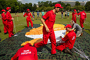 The Trump Baby sitting team dressed in red boiler suits put up the six metre high inflatable TrumpBaby balloon for the demo on the Meadows in Edinburgh for the Scottish demonstration. United Kingdom. 14th July 2018.