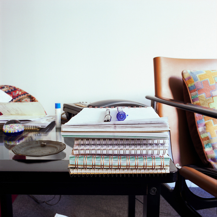 Looking at a stack a papers and two pens on top of them, sitting on a black table. There are a chair and colorful pillow on the right, the edge of a pillow in the left background; a black phone is behind the paper stack, and a small tray, a Lip Shtick brand stick, and a small glass paperweight are on the left of the stack.