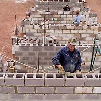 Keith Ford lays cinderblocks to support new bleachers at the Uranium Capital Speedway in Milan Saturday.