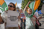 Femalecampaigners wearing traditional saris waving Kashmiri Pakistan flags protest outside Houses of Parliament on the 29th August 2019 in London in the United Kingdom.