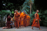 """monks receiving rice offerings  in Luang Prabang, Laos, a UNESCO World Heritage Center..with the """"Tree of Life"""" painting on the front.."""