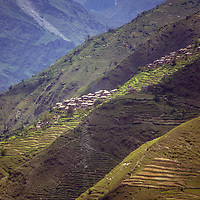 Hand-carved rice paddies cover hillsides in the foothills of the Nepal Himalaya below Annapurna.