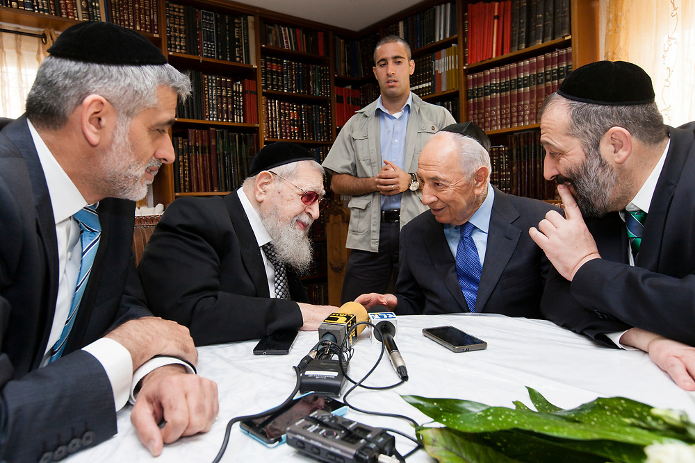 Israel's President Shimon Peres (sitting 2nd R) speaks with Spiritual leader of the Ultra-Orthodox Shas party, Rabbi Ovadia Yosef (sitting 2nd L) as Shas party parliament member Aryeh Deri (R) and Shas party parliament memebr Eli Yishai (L) look on, during the Israeli President's traditional Passover holiday visit at the Rabbi's residence in Jerusalem, Israel, on March 31, 2013.