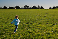 Young girl running in grass field, Cesar Chavez City Park, Berkeley Waterfront, Alameda County, California