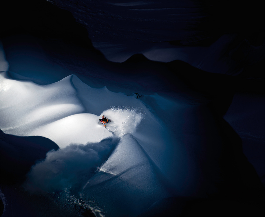 Illumination<br /> <br /> Travis Rice slashes a snow wave near the end of the day in the Tordrillo Mountains of Alaska while filming for the Art of Flight movie. This was the last image I took after more then 4 weeks of shooting and sleeping in the mountains. This photo won the illumination category in the Red Bull Illume photo contest. <br /> <br /> <br /> For info on this photograph:<br /> <br /> I had been in the Tordrillo Mountains for 4 weeks with the Brain Farm Cinema crew documenting the making of the Art of Flight movie. From day one I had it in my mind that I wouldn't leave without shooting a photo from a hovering helicopter looking straight down on a rider. Unfortunately setting up this kind of shot was much more complicated then I originally thought. We had 2 helicopters on this trip. The first was the film ship, fitted with a Cineflex aerial camera to the nose. It's important for this ship to be as light as possible so that it could manoeuvre quickly so I wasn't allowed to shoot from that one. The second helicopter was the riders ship. It would shuttle the riders around getting them on top of the lines they wanted to ride and would pick them up at the bottom. As a photographer I would use this ship to move myself around when it wasn't possible to snowboard there. So when I found the right terrain to shoot my aerial photo, I had to coordinate the move I wanted to make with the film ship as it would generally fly all over the place to get the best shot of the entire line. In the end we decided I would just hover above the line, hang out the side and shoot while the film ship would do its thing around us. This was the best way to keep both helicopters from crashing into each other.<br /> <br /> Once I was harnessed in and hanging out of the helicopter, we lifted up and hovered a few 100 feet above the line. Travis was called in to drop and made this single turn before disappearing over the edge. It would have been nice to follow him down the whole line but 