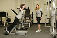 Monroe, New York - A instructor watches a woman work out with weights at the new South Orange Family YMCA on Wednesday, Feb. 16, 2011.