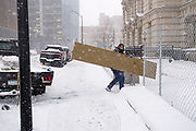 29 DECEMBER 2020 - DES MOINES, IOWA: A worker carries a piece of plywood into a construction site during the heaviest snowfall so far of the 2020-21 winter. Des Moines was expected to get about 8 inches of snow before Wednesday morning. Statewide, across Iowa, more than 900 snowplows have been called out to clear the roads.       PHOTO BY JACK KURTZ