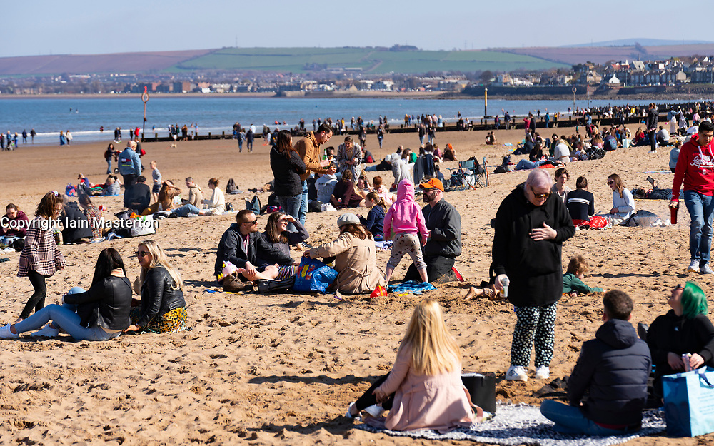 Portobello, Scotland, UK. 3 April 2021. Easter weekend crowds descend on Portobello beach and promenade to make the most of newly relaxed  Covid-19 lockdown travel restrictions and warm sunshine with uninterrupted blue skies. Pic; Beach busy with members of the public in small groups. Iain Masterton/Alamy Live News