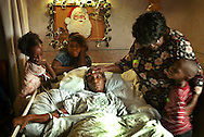 Priscilla Lipscomb, who suffers from cervical cancer, lays in bed at Brookwood Gardens Convalescent Center in Homestead surrounded by her children and her mother. Left to right are, Tynisia McIntyre, 7, Lasaunda Lipscomb, 9, Pricilla's mother, Sue Lipscomb and Tyrell McIntyre, 6.