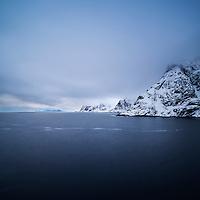 Snow covered mountains rise from sea, Å, Moskenesøy, Lofoten Islands, Norway