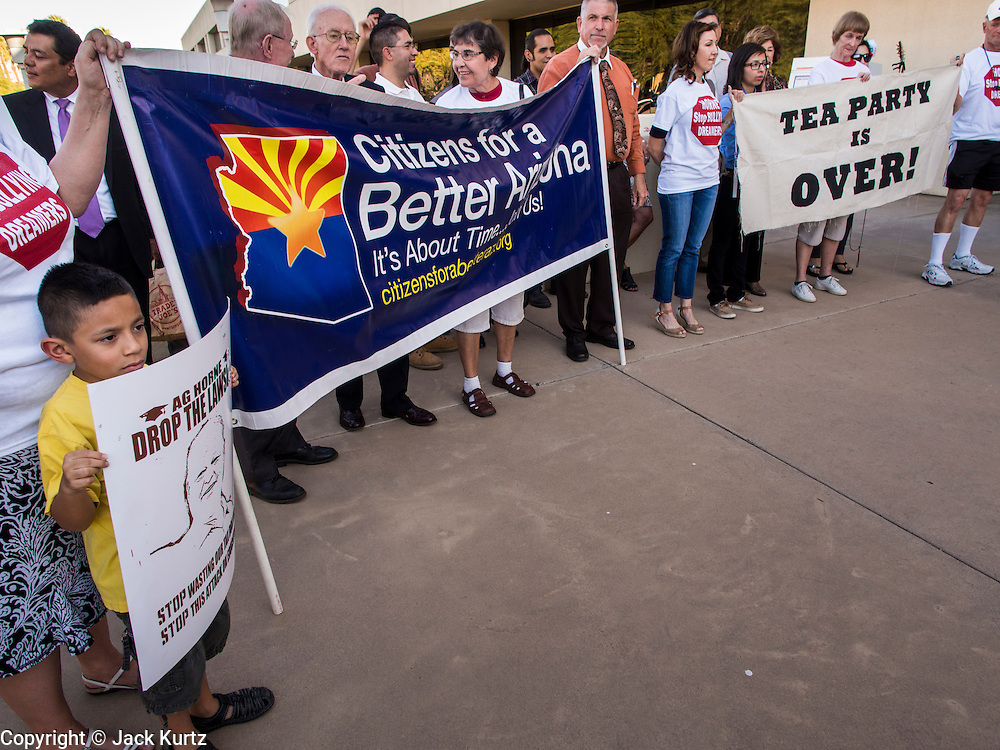 17 OCTOBER 2013 - PHOENIX, AZ: ANDRES GARCIA, 6, (far left) and others gather in front of the office of the Arizona Attorney General. About 100 people came to the office of Arizona Attorney General Tom Horne to protest the decision by Horne to sue community colleges in Maricopa County that charge DREAM Act students who are residents of Arizona out of state tuition rather than in state resident tuition. Nearly 10 people were arrested in a planned civil disobedience during the protest.      PHOTO BY JACK KURTZ