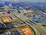 Nederland, Noord-Holland, Amsterdam; 17-04-2021; Zuidas, begin ring A10, A10 Zuid. Zicht op de Schinkelbruggen, spoorlijn met intercity richting Schiphol. Aan gene zijde van de A10 het IJsbaanpad met woonschepen en de Nieuwe Meersluis. Onder in beeld jachthavens in de Nieuwe Meer. <br /> Zuidas, start of ring A10, A10 South. View of the Schinkel bridges, railway with intercity to Schiphol. On the other side of the A10 the IJsbaanpad with houseboats and the Nieuwe Meersluis. At the bottom of the picture marinas in the Nieuwe Meer.<br /> <br /> luchtfoto (toeslag op standaard tarieven);<br /> aerial photo (additional fee required)<br /> copyright © 2021 foto/photo Siebe Swart