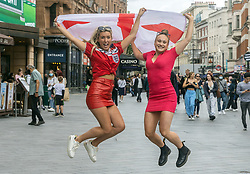 Licensed to London News Pictures. 07/07/2021. London, UK. Jump for joy. England fans (L) Emily Merritt 19 and Abbey Kidd 21 from Dartford cheer and wave a flag in Leicester Square, London ahead of the Euro 2020 semi-final between England and Denmark at Wembley tonight for a place in the finals this Sunday (11 July 2021). Today, England taken on Denmark in the first semi-final since 1996 as eager fans start to gather in London. Photo credit: Alex Lentati/LNP