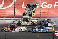 Matt Crafton (88) flips his truck on the back stretch after being involved in a mult-truck collision on the final lap during a NASCAR truck series auto race at Daytona International Speedway, Friday, Feb. 24, 2017, in Daytona Beach, Fla. (AP Photo/Phelan M. Ebenhack)