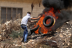 NABLUS, July 28, 2017 - Nablus, West Bank, Occupied Territories -  A Palestinian protester burns a tire during clashes after a protest against the expanding of Jewish settlements in Kufr Qadoom village near the West Bank city of Nablus. (Credit Image: © Nidal Eshtayeh/Xinhua via ZUMA Wire)