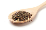Ground Black pepper (Piper nigrum) on a wooden kitchen spoon on white Background