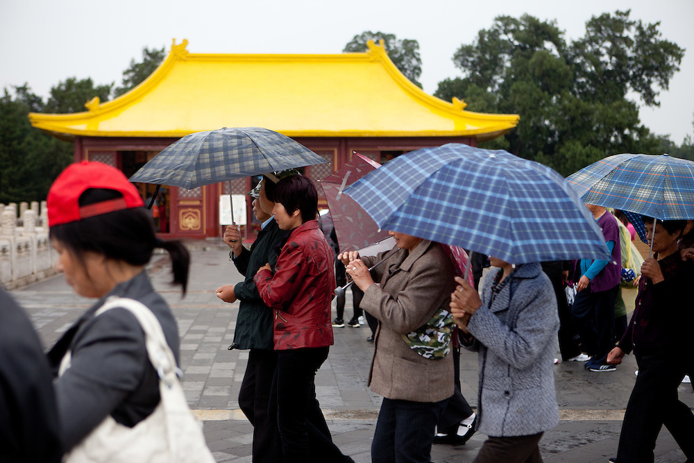 """A group of tourists with umbrellas at """"The Temple of Heaven"""" which is a complex of Taoist buildings situated in the southeastern part of central Beijing. Beijing is the capital of the People's Republic of China and one of the most populous cities in the world with a population of 19,612,368 as of 2010."""