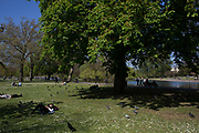People relaxing in Spring sunshine in Regent's Park, London, UK.