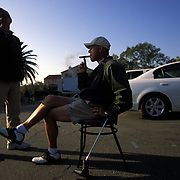 """Waiting in the parking lot at famed Riviera Country Club in Los Angeles, longtime pro caddies David Patterson, better known by his caddy name """"Alaska Dave,"""" seated, and Jerry Knapp scan the horizon for incoming PGA Tour players in hopes of finding work for the week."""
