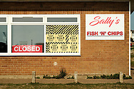 Sally's fish n chips takeaway on Sea Gate road in Hunstanton. A large close sign is displayed in the window next to a large amount of hazard tape & social distancing signage. Taken on the last hot day of the Summer in Hunstanton Norfolk, the first summer in the UK during the COVID-19 pandemic.<br /> <br /> Photo by Jonathan J Fussell, COPYRIGHT 2020