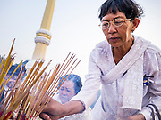 """31 JANUARY 2013 - PHNOM PENH, CAMBODIA:  A Cambodian woman lights incense during a prayer vigil for former King Norodom Sihanouk. Sihanouk (31 October 1922- 15 October 2012) was the King of Cambodia from 1941 to 1955 and again from 1993 to 2004. He was the effective ruler of Cambodia from 1953 to 1970. After his second abdication in 2004, he was given the honorific of """"The King-Father of Cambodia."""" Sihanouk served two terms as king, two as sovereign prince, one as president, two as prime minister, as well as numerous positions as leader of various governments-in-exile. He served as puppet head of state for the Khmer Rouge government in 1975-1976. Most of these positions were only honorific, including the last position as constitutional king of Cambodia. Sihanouk's actual period of effective rule over Cambodia was from 9 November 1953, when Cambodia gained its independence from France, until 18 March 1970, when General Lon Nol and the National Assembly deposed him. Upon his final abdication, the Cambodian throne council appointed Norodom Sihamoni, one of Sihanouk's sons, as the new king. Sihanouk died in Beijing, China, where he was receiving medical care, on Oct. 15, 2012. His funeral procession, which will wind through Phnom Penh is Friday, Feb.1 and his cremation is on Feb. 4, 2013. Over a million people are expected to attend the service.    PHOTO BY JACK KURTZ"""