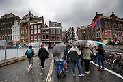 Toeristen staan in de regen te luisteren naar hun gids bij het Rokin in Amsterdam.<br /> <br /> Tourists listen to the guide at the Rokin in Amsterdam in the pouring rain.