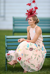 A female racegoer sits on a bench during day three of Royal Ascot at Ascot Racecourse.