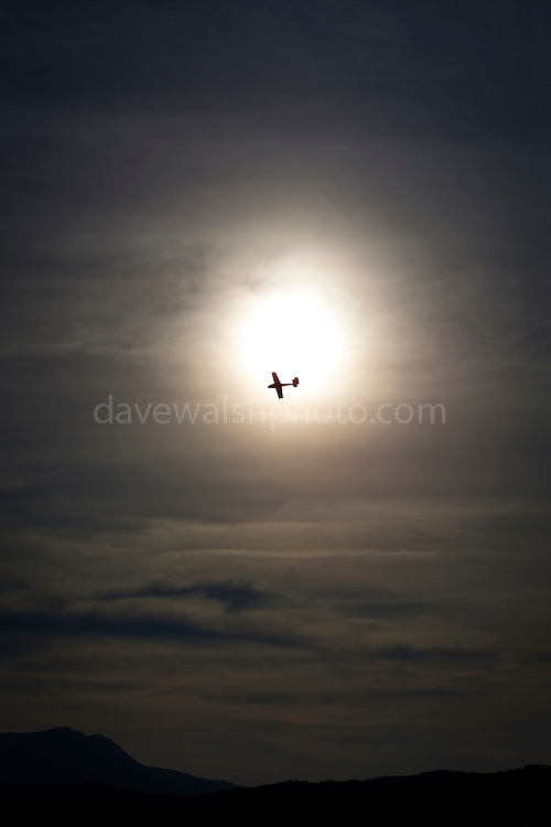 """A glider flies past the sun at Cap Bear, near Port Vendres, France. This mage can be licensed via Millennium Images. Contact me for more details, or email mail@milim.com For prints, contact me, or click """"add to cart"""" to some standard print options."""