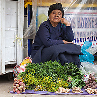 A woman selling different vegetables at a market in Tarma.
