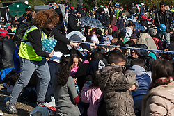 Š Licensed to London News Pictures. 24/10/2015. Rigonce, Slovenia. Migrants are waiting to be escorted to the camps in Dobovo and Brezice, Slovenia at the Slovenian Croatian border. Volunteers are giving water to migrants. Photo: Marko Vanovsek/LNP