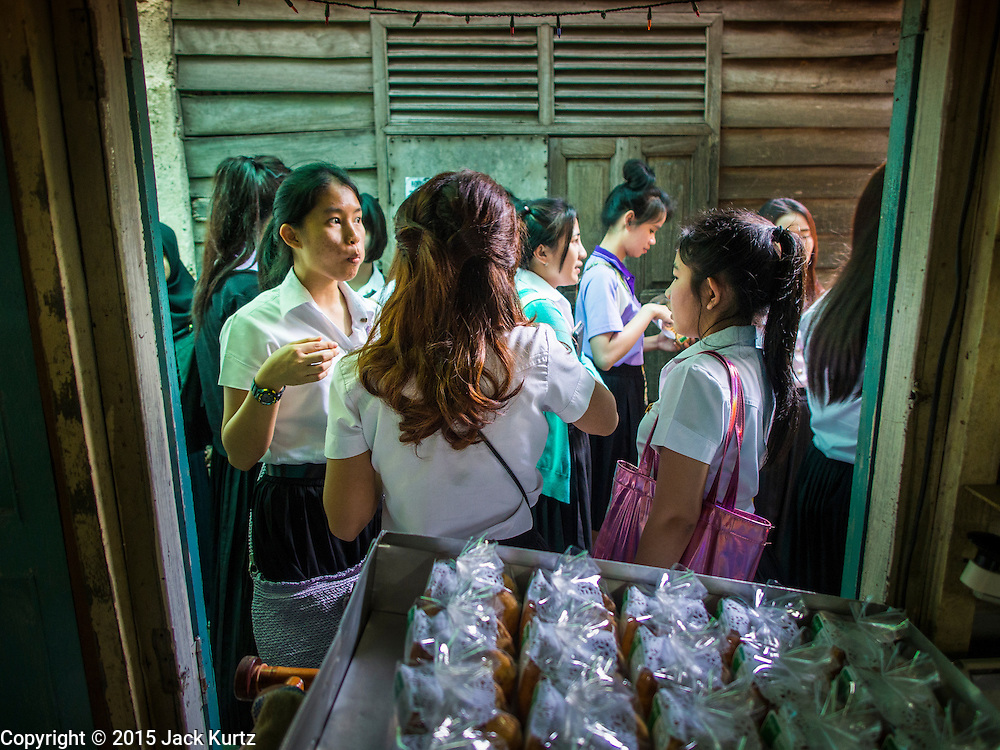 """06 FEBRUARY 2015 - BANGKOK, THAILAND: University students buy fresh baked cakes at the walkup window at Thanusingha Bakery, a bakery that specializes in traditional Thai Catholic desert cakes. The cakes are called """"Kanom Farang Kudeejeen"""" or """"Chinese Monk Candy."""" The tradition of baking the cakes, about the size of a cupcake or muffin, started in Siam (now Thailand) in the 17th century AD when Portuguese Catholic priests accompanied Portuguese soldiers who assisted the Siamese in their wars with Burma. Several hundred Siamese (Thai) Buddhists converted to Catholicism and started baking the cakes. When the Siamese Empire in Ayutthaya was sacked by the Burmese the Portuguese and Thai Catholics fled to Thonburi, in what is now Bangkok. The Portuguese established a Catholic church near the new Siamese capital. Now just three families bake the cakes, using a recipe that is 400 years old and contains eggs, wheat flour, sugar, water and raisins. The same family has been baking the cakes at the Thanusingha Bakery, near Santa Cruz Church, for more than five generations. There are still a large number of Thai Catholics living in the neighborhood around the church.        PHOTO BY JACK KURTZ"""
