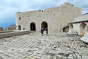 Woman and child walking across paved area toward small tower, Fortress Lovrinjenac (Fort of Saint Lawrence), Dubrovnik old town, Croatia