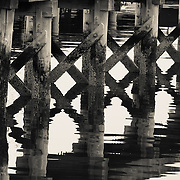 Gloucester, MA, USA. April 14, 2015 Relections of the supports of an old pier in the fishing port.