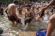 Hinduiska pilgrimer badar i den heliga floden i Erumeli, på väg till det heliga templet i Sabarimala. För att helt uppgå i pilgrimsvandringen, ge upp sitt eget ego och för att hedra Lord Ayyappa, målar pilgrimerna sina kroppar och bär vapen i trä. Traditionen kallas pettatullal. Både hinduer och muslimer anser att Erumely är en helig stad.  <br /> <br /> Hindu pilgrims bathe in the holy river in Erumeli, the Kottayam district of Kerala, India. In order to give up their egos and to surrender to Lord Ayyappa, the Hindu pilgrims paint their bodies and carry weapons made of wood on the way to Sabarimala. Erumely is considered holy by both Hindus and Muslims.<br /> <br /> Copyright 2016 Christina Sjögren, All Rights Reserved