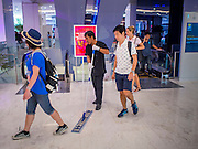 """27 MARCH 2015 - BANGKOK, THAILAND: A maintenance worker cleans around shoppers in """"EmQuartier,"""" a new shopping mall in Bangkok. """"EmQuartier"""" is across Sukhumvit Rd from Emporium. Both malls have the same corporate owner, The Mall Group, which reportedly spent 20Billion Thai Baht (about $600 million US) on the new mall and renovating the existing Emporium. EmQuartier and Emporium have about 450,000 square meters of retail, several hotels, numerous restaurants, movie theaters and the largest man made waterfall in Southeast Asia. EmQuartier celebrated its grand opening Friday, March 27.   PHOTO BY JACK KURTZ"""