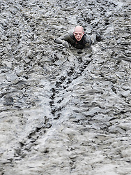 © Licensed to London News Pictures. 12/05/2019. Maldon, UK. A competitor is surrounded by a sea of mud as he takes part in the Maldon Mud Race in Essex. The race originated in 1973 and involves competitors racing around a course on the mudbanks of the river Blackwater at low tide. Photo credit: Peter Macdiarmid/LNP