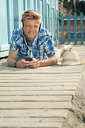 Teenager lying on front beach listening music