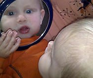 Talus looks in the mirror at ten months old