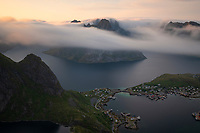 Sea fog rolls though fjords and over mountain peaks from summit of Reinebringen, Moskenesøy, Lofoten Islands, Norway